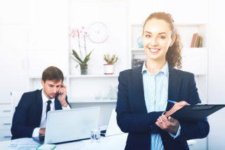 オフィスでクリップボードを持つ笑顔の女性