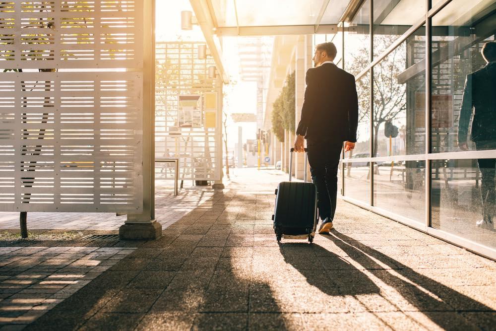 スーツケースを引きながら歩くスーツを着た男性