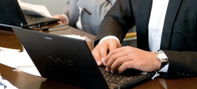 ノートパソコンを操作するスーツの男性の手元
