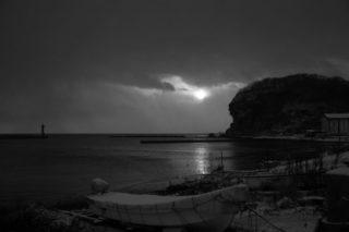 月明かりに照らされた夜の海と小舟