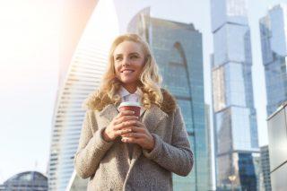 オフィス街の中心で朝日を見つめる笑顔の女性