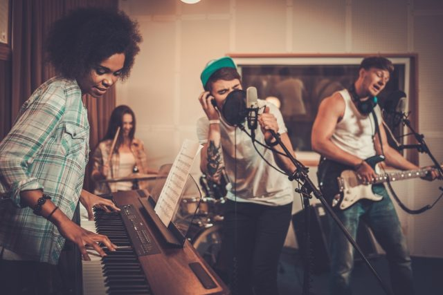 スタジオで歌を収録しているバンドマン達