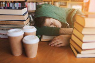 図書館で居眠りをする男性
