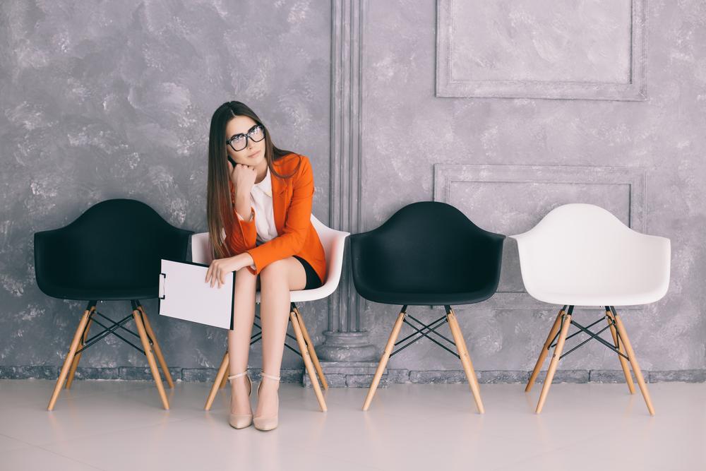 書類を持って真剣な顔で椅子に腰掛ける、オレンジ色のジャケットを着た女性