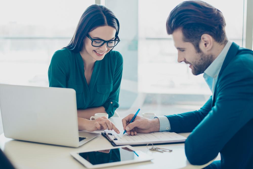 書類作成中の男性と、アドバイスをする女性