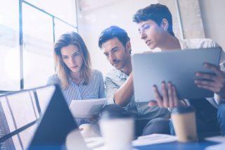 ノートパソコンを見比べながら話し合う仕事中の男女