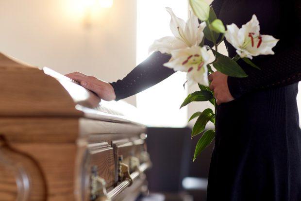 百合の花を持ち、棺桶に手を添える黒い服を着た男性