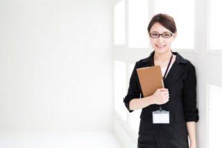 にこやかに笑う、書類を抱えたメガネの女性