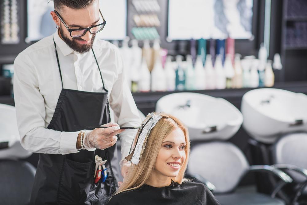金髪の女性にカラーリングをする美容師