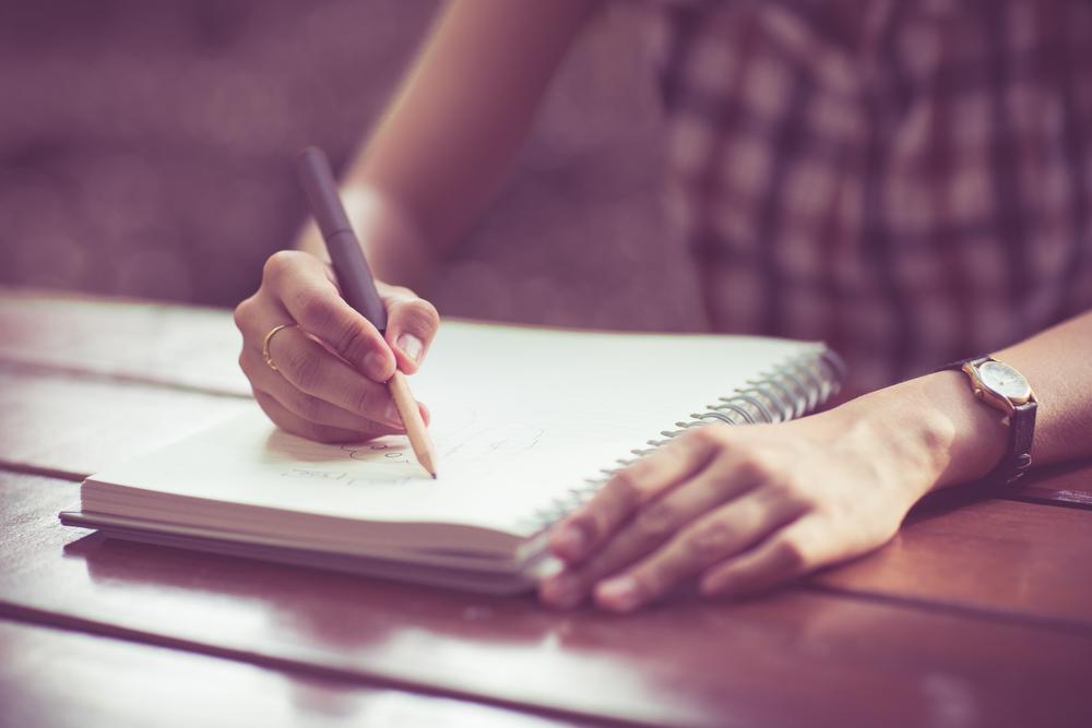 ノートに自分のことを書く女性
