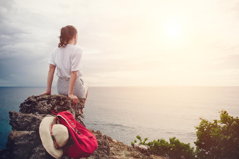 海辺の岩に座り遠くを見つめる女性