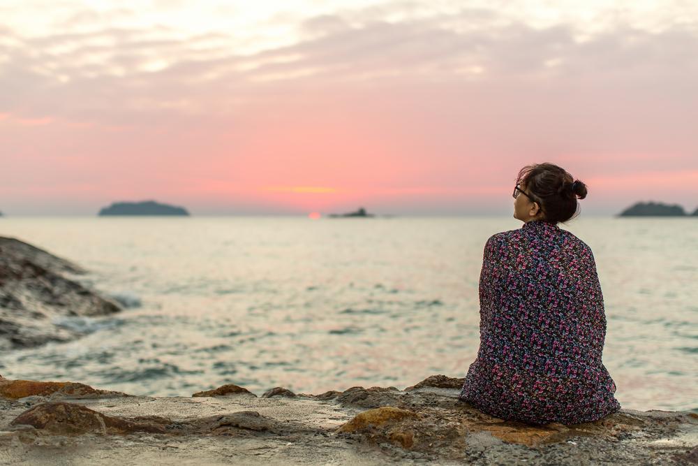 海辺でに座って夕日を眺める若い女性