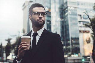 テイクアウトのコーヒーを持って佇む、黒いスーツを着た男性
