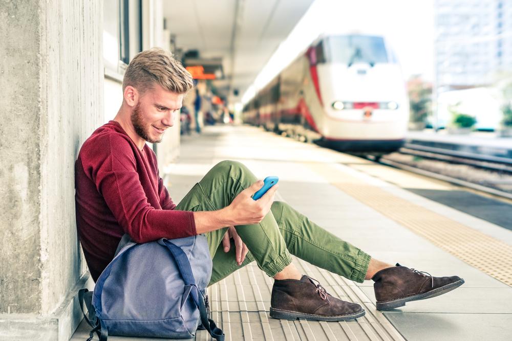 高速鉄道のホームに座り、スマートフォンを見る笑顔の男性