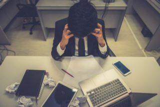 机の上に物を散乱させ、頭を抱えるスーツの男性