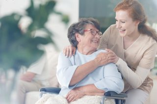 車いるの高齢女性と介助する若い女性