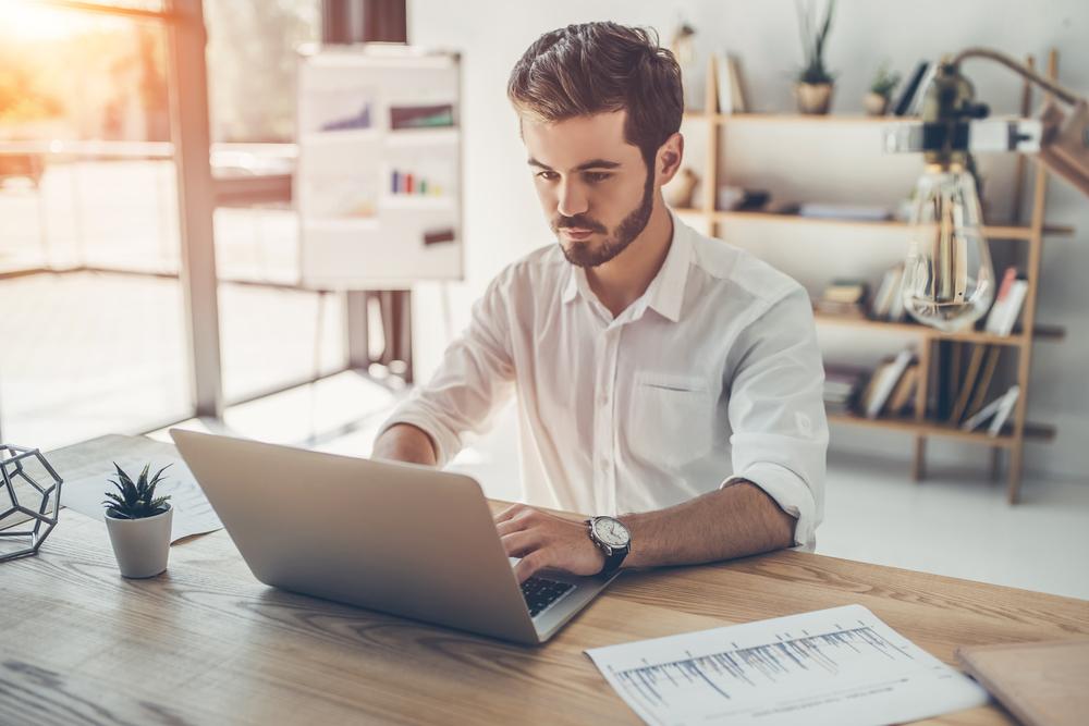 ノートパソコンでタイピングする男性