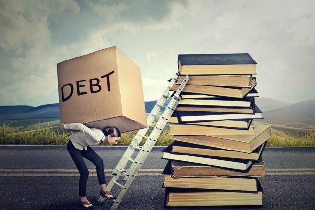 「DEBT」と書かれた大きな段ボールを背負い、ハシゴで積み上げられた本を登る女性