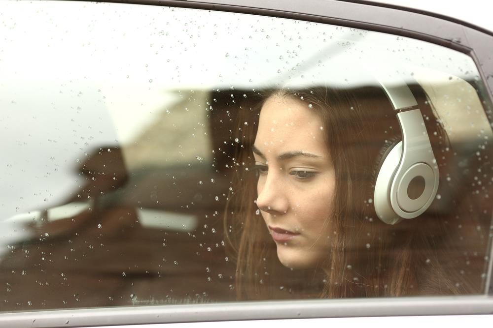 雨粒でぬれる車の窓と、車内で疲れたように俯く女性