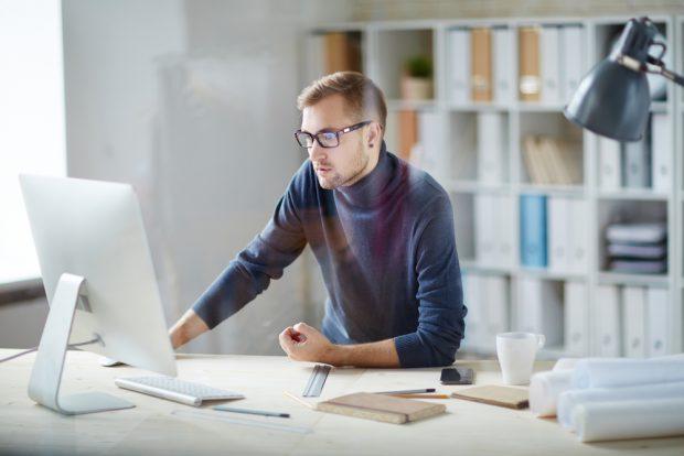 パソコンを操作するメガネをかけた男性