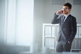 オフィスの中で携帯電話で話す、濃いグレーのスーツを着た男性