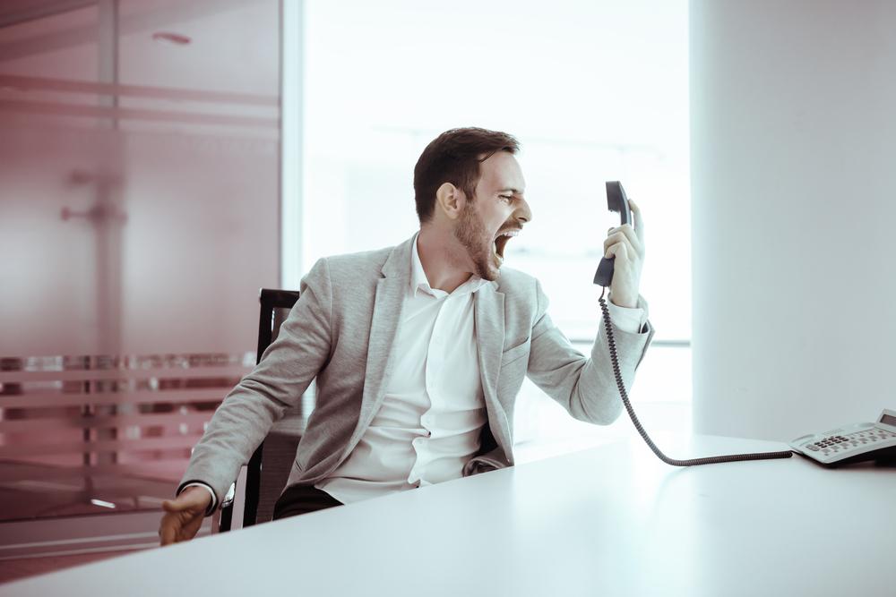 電話相手に怒鳴り散らす男性