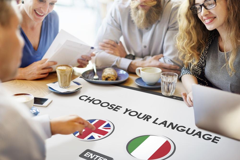 「CHOOSE YOUR LANGUAGE(言語を選んでください)」と書かれた紙を眺める人達