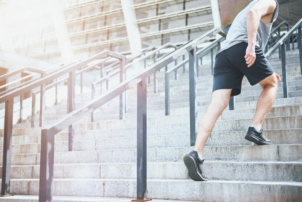 屋外の階段を駆け上がるスポーツウエアを着た男性