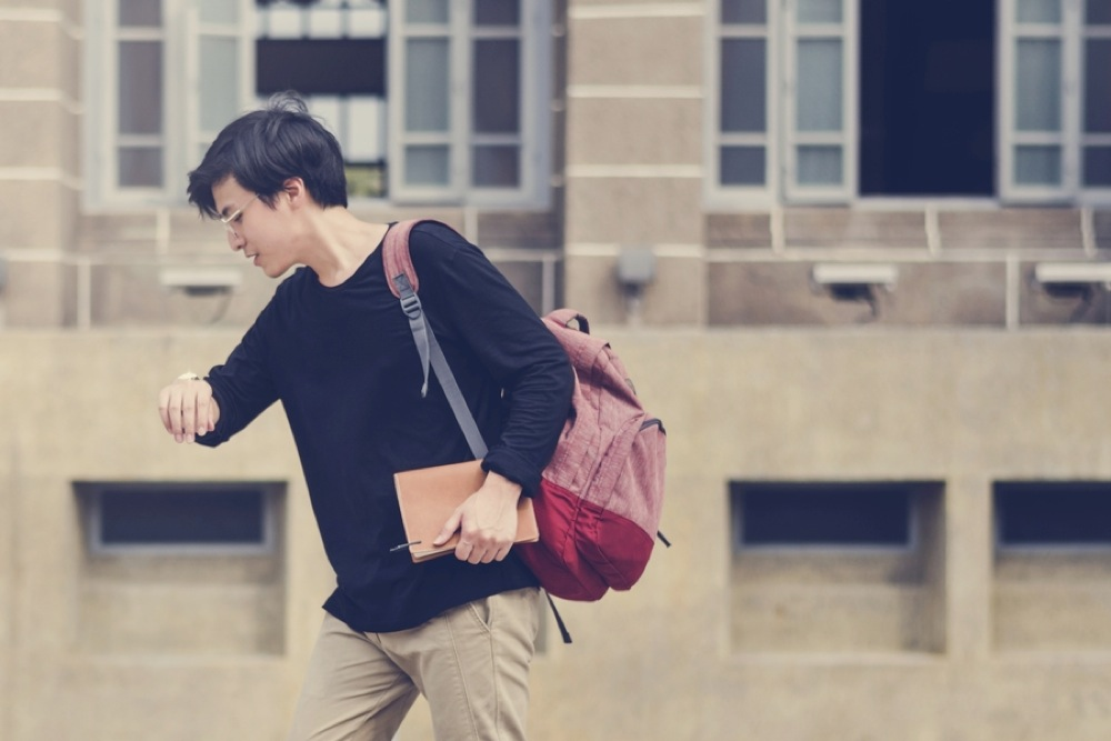 時計を見ながら走る学生