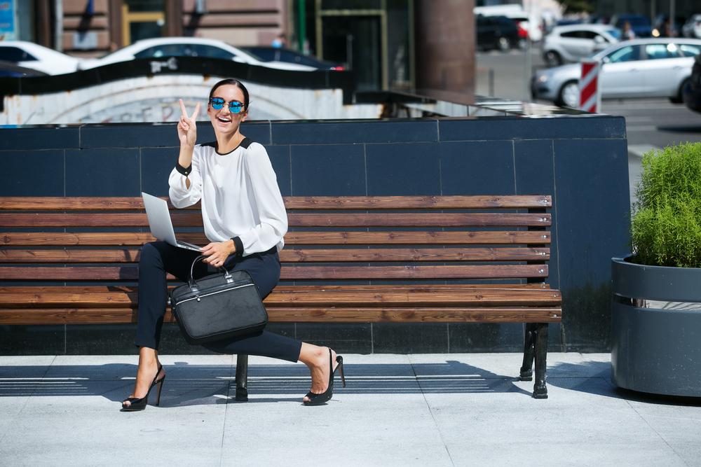 木製のベンチに座ってピースするサングラスをかけた女性