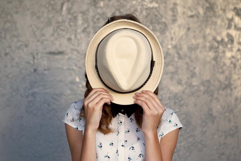 白い帽子で顔を隠すシャイな女性