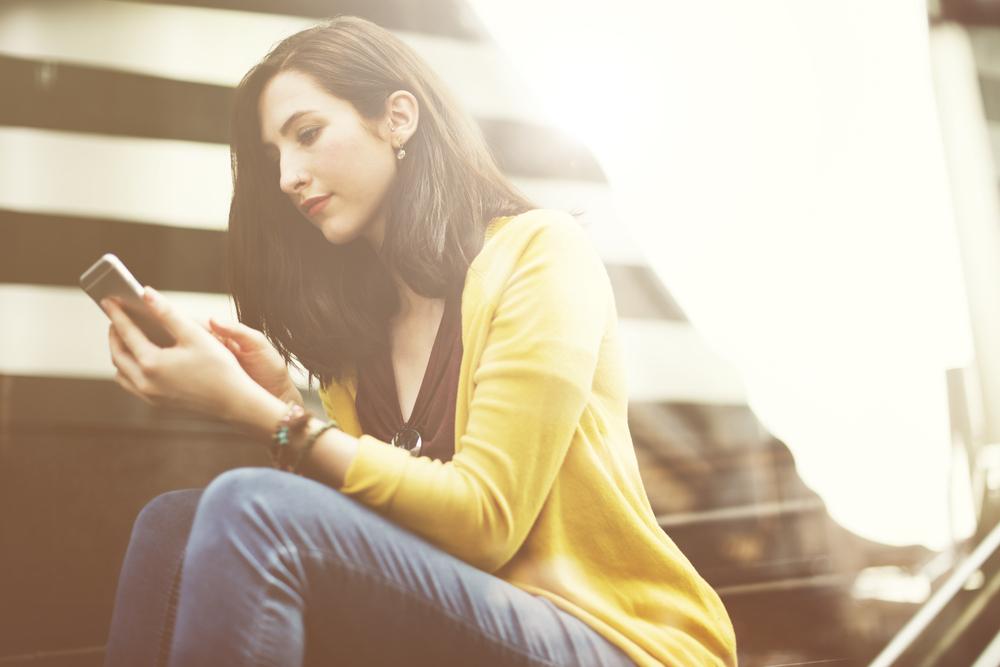 スマートフォンを真剣な表情で見る私服姿の女性