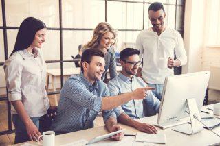 パソコンを見ながら笑顔で話し合うオフィスの仲間
