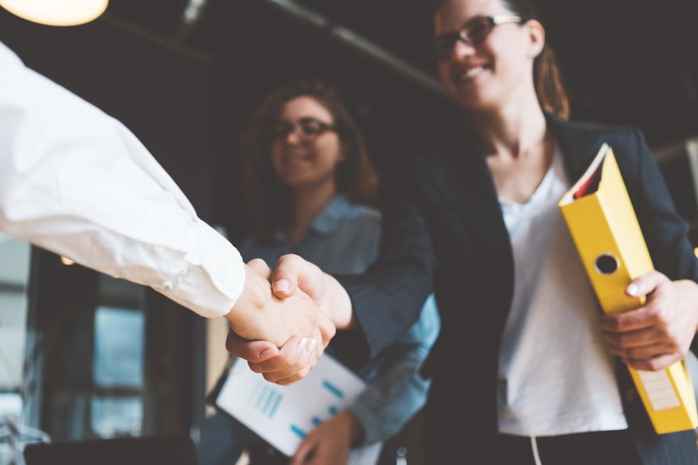 握手をする営業職の女性