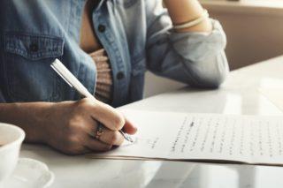 考えながら手紙を書く女性