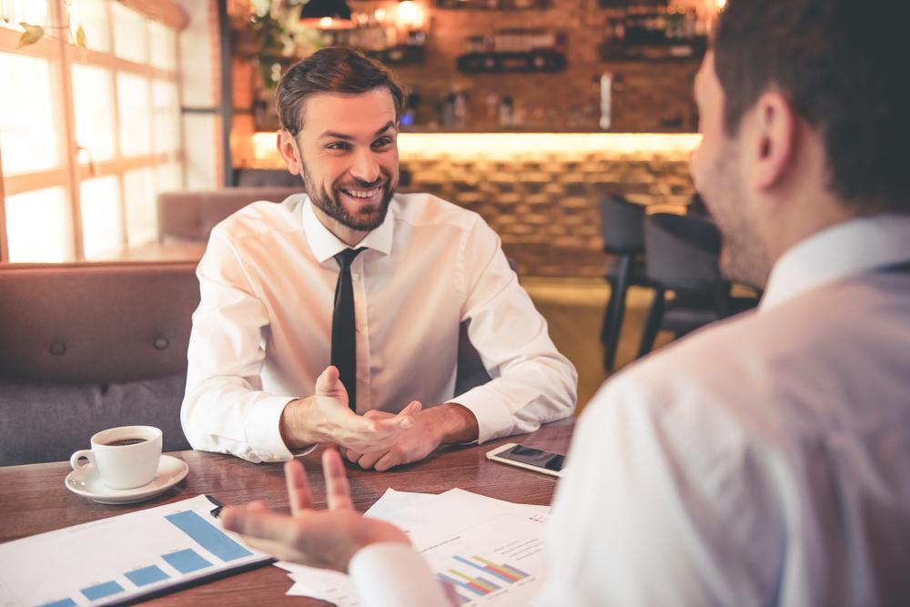 カフェで談笑しながらビジネスの話を進める男性2人