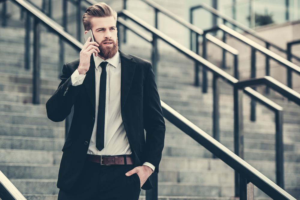 屋外の階段で立ち止まり通話する、黒いスーツを着た男性