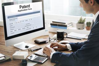 patent application form(特許申請書)と書かれたPC画面をみる男性