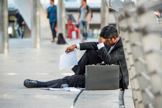 街中に座り込み、頭を抱えるスーツを着た男性