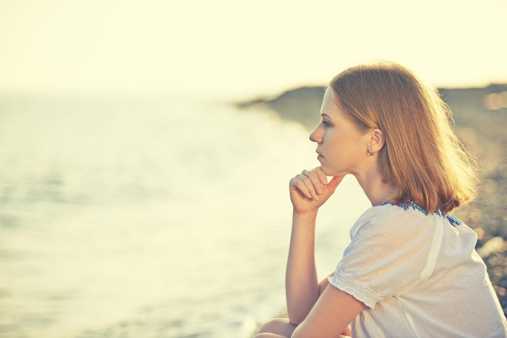 一人で静かに海を眺める白人の女性