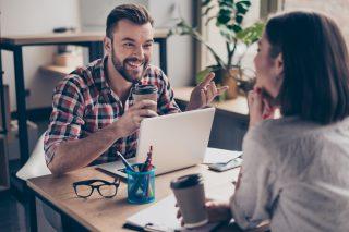 コーヒーを飲みながら楽しそうに会話する仕事中の男女