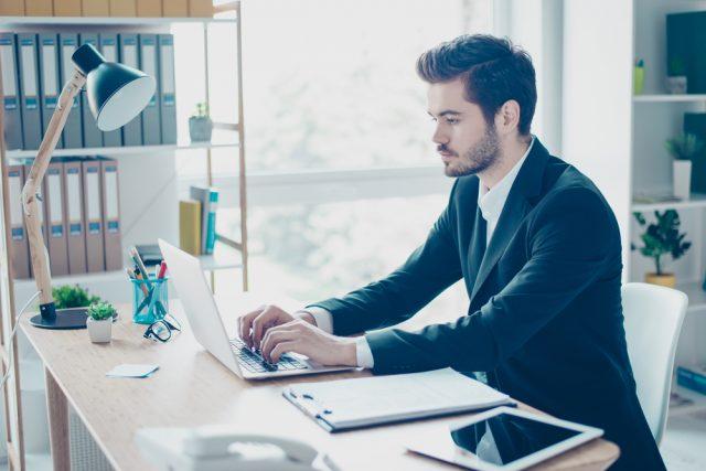 スーツを着てノートパソコンを操作する男性
