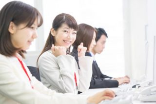 オフィスでガッツポーズをしながら笑う女性