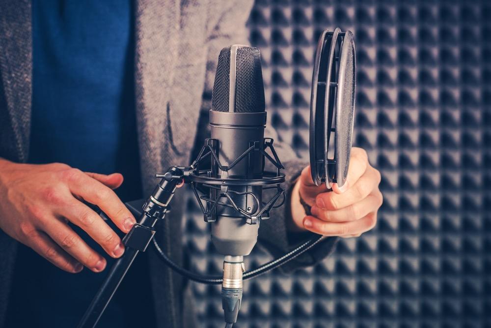 マイクを使って仕事をする収録用のスタジオにいる男性