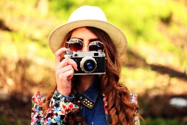 フィルムカメラで写真を撮る、サングラスに麦わら帽子を身につけた女性
