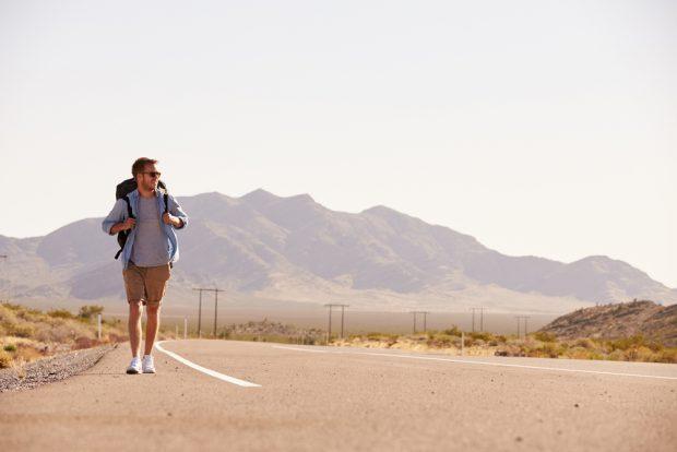 大きなバックパックを担いて何もない道路を歩く男性