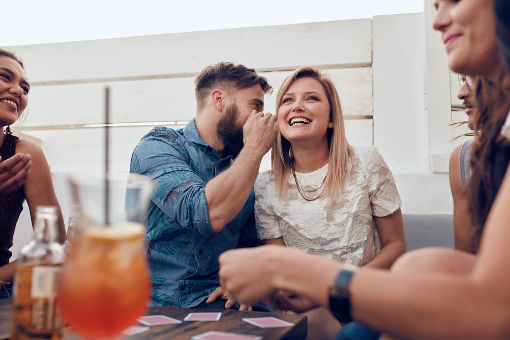 飲み会の最中に女性に耳打ちする男性