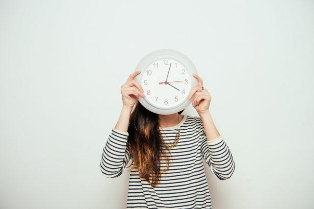 自分の顔に時計をあて、過ぎ行く時間を表す女性