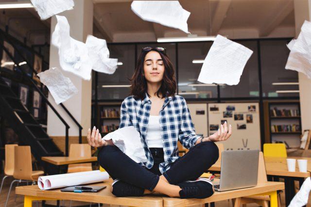 オフィスの机の上であぐらをかいてヨガのポーズをとる女性