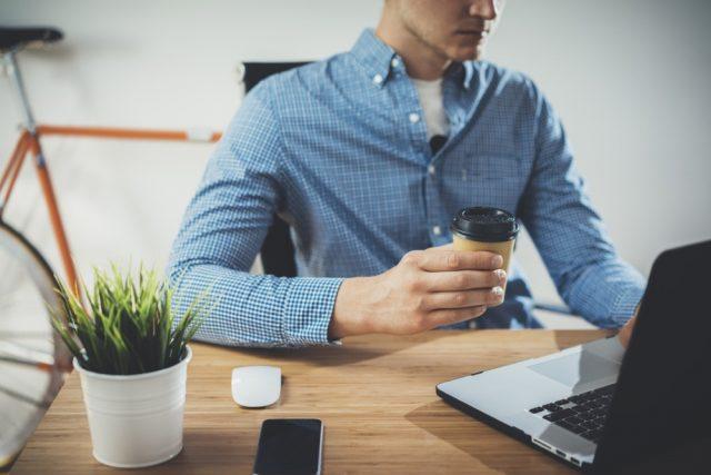 青いチェックのシャツを着てノートパソコンに向かい仕事をするエンジニア風の男性